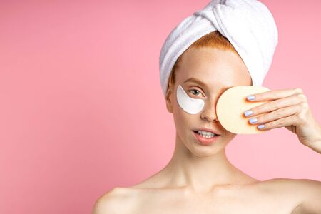 Closeup of cheerful female model with fresh soft skin, white towel on head, covering eye with cosmetic sponge, applying collagen patches, enjoying skin care procedures on pink background. Copy space.