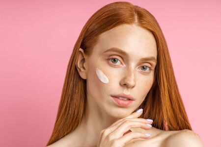 Closeup headshot beauty portrait of young woman with cream on cheek. Attractive caucasian woman with red hair, clean fresh freckled skin, touching chin looking camera against pink wall.
