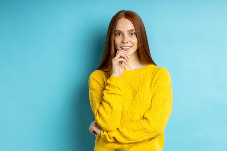 Studio shot of redhead caucasian young woman isolated blue background