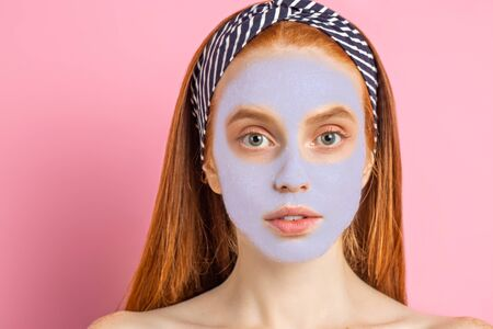 Beautiful woman with facial mask on pink background Imagens