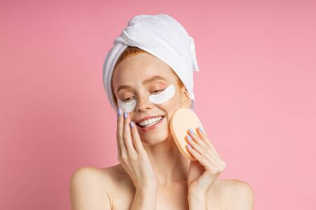 Happy redhead freckled european woman with hydrogel patches under eyes for reduce puffiness, holding cosmetic sponge near face, wearing white towel on head standing against pink wall. 版權商用圖片
