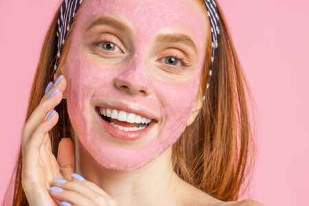 Headshot of pretty cheerful caucasian woman touching face gently, applying peeling mask, showing bare shoulders, standing against pink wall. Beauty treatments, spa at home.
