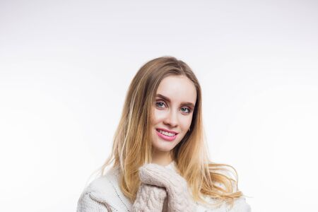 Happy blonde woman wearing beige sweater, knitted mittens and smiling at camera on white isolated background with copy space. Winter, Christmas, cozy concept