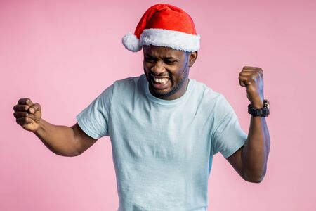 Angry furious african man clenching fists and teeth, raising hands, wearing t shirt, Santa hat, plans for Christmas didn't come true, posing on pink background. Negative emotions, facial expressions.
