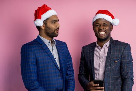African american and indian man, wearing formal wear, standing against pink wall. Two colleagues in Santa hats, cheerfully communicating during break, having fun, laughing, using mobile phone.