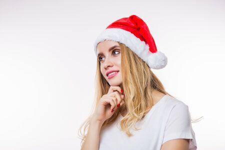 赤いサンタの帽子とコピースペースで白い背景に横に笑顔で見てTシャツを着て幸せな魅力的なブロンドの女性。クリスマス、新年、お祝いのコンセプト