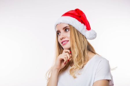 Happy charming blonde woman in red Santa hat and t-shirt looking with smile to the side on white background with copy space. Christmas, new year and celebration concept