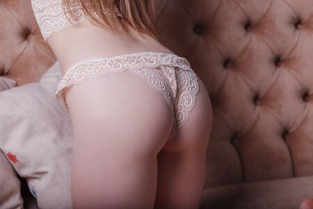 beautiful blonde girl in delicate beige lace underwear bent over on a brown sofa rear view close-up priests