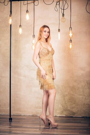 Full length portrait elegant sexy blonde woman in short gold dress in the Studio. Party, holiday, celebration, new year, Christmas, birthday concept Stock Photo