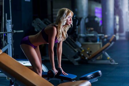 beautiful sexy blonde girl a slim, purple linen has been in the gym, profile, dumbbells in hands, horizontal, copyspace, sports, fitness, cross fit 版權商用圖片