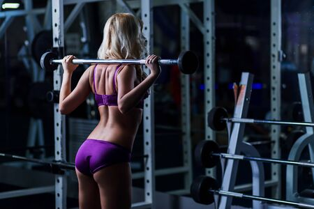 blonde girl with a slender figure, tanned skin in purple lingerie squats with dumbbells on the hands, back, butt, gym, fitness club, cross fit Zdjęcie Seryjne