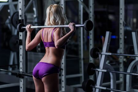 Blonde girl in purple lingerie deals in fitness from the back, dumbbell, squat, sport