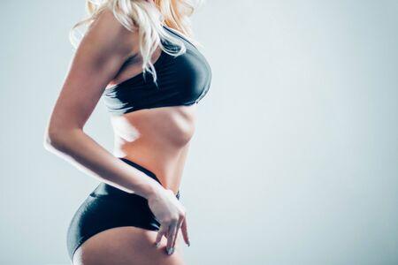 beautiful slim figure, blonde girl in a black sports underwear profile, isolate, close-up, copyspace