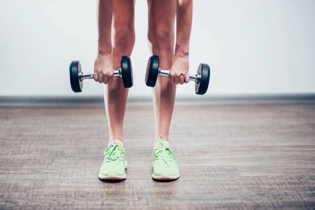 black large dumbbell in the hands of the girls legs in green shoes, and bent down to the floor, closeup, white background