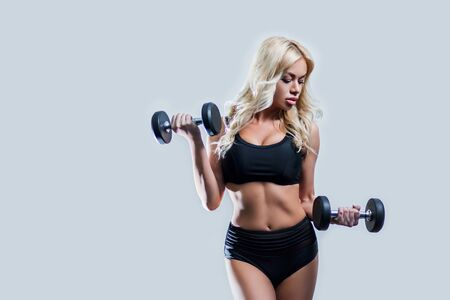 beautiful blonde girl slim figure, with makeup, in a black sports underwear is with dumbbells in hands, looking down, gray background, isolate, fitness, cross fit, sports,