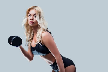 beautiful blonde girl slim figure, with makeup, in a black sports underwear is with dumbbells in hands, looking down, isolate, fitness, cross, fit, sports, Zdjęcie Seryjne
