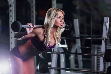 very beautiful, sexy blonde girl with a slender figure, tanned skin in purple lingerie squats with dumbbells on the hands, profile, cute face, horizontal, in a gym, fitness club, cross fit Zdjęcie Seryjne