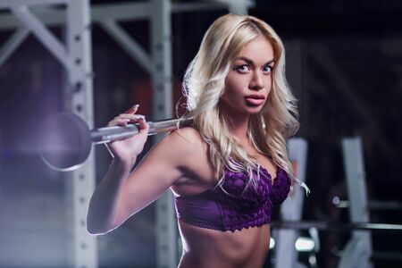 very beautiful sexy girl, model, blonde with tanned skin in a purple underwear in gym squatting with kettlebells, dumbbells, close-up, looking at camera, fitness, cross fit, sport, healthy lifestyle