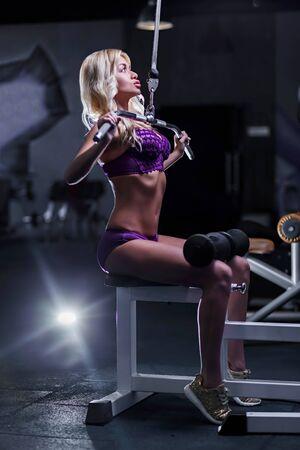the girl athlete, blonde, pretty sexy model pulled in the gym, pumping muscles of the hands while sitting in purple linen and gold sneakers, cross, fit, fitness, dark background