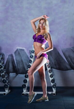 very beautiful, sexy blonde girl with a shapely, more muscular figure, tanned skin in purple linen, with Golden sneakers is full-length, elegantly posing in the gym, fitness club, cross fit, Stock Photo