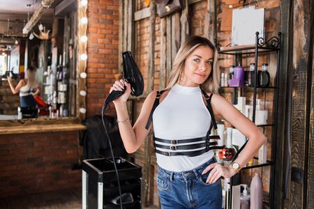 Beautiful smiling blond hairdresser with hairdryer stands and looks at the camera in the beauty salon