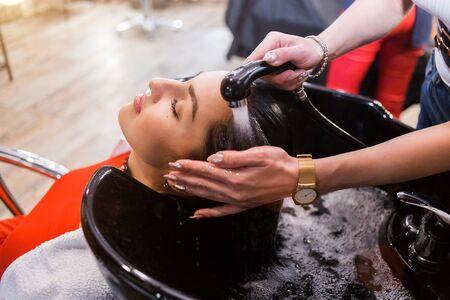 Spa hair treatment, hairdresser applies a white mask to the clients long dark hair Фото со стока