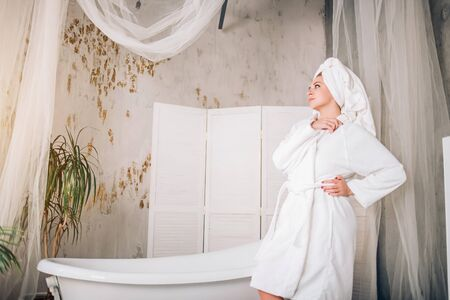 Young beautiful spa woman wearing white bathrobe and towel on head standing near bathtub in modern bathroom with loft interior looking to side thinking, making plans witn serious expression