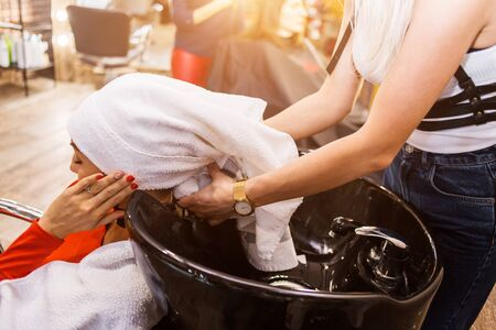 Spa treatments, beautician, hairdresser. Beautiful female client on the chair after washing hair wrapped her head in a white towel.