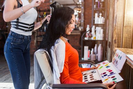 Beautiful client woman picks up hair color in a beauty salon. Hairdresser making hairstyle.