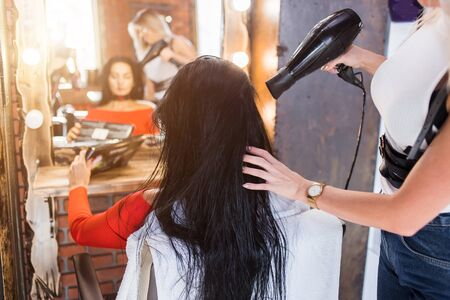 Professional hairdresser with hairdryer dries hair in beauty salon.