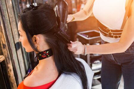 Professional hairdresser drying hair with hairdryer in a beauty salon