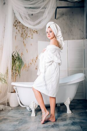 Full length portrait of sensual elegant woman in spacious modern bathroom. Side view of blonde spa caucasian girl with towel on head, wearing white bathrobe after having bath, looking at camera.