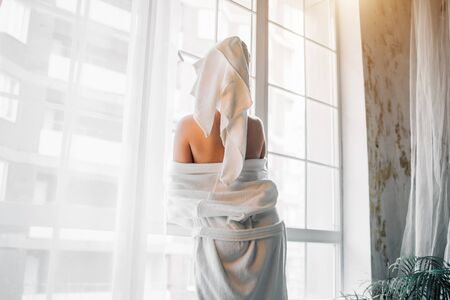 Backside portrait of slim caucasian woman with white towel on head standing against the big window in bathroom after having bath, taking off her bathrobe, showing bare shoulders.