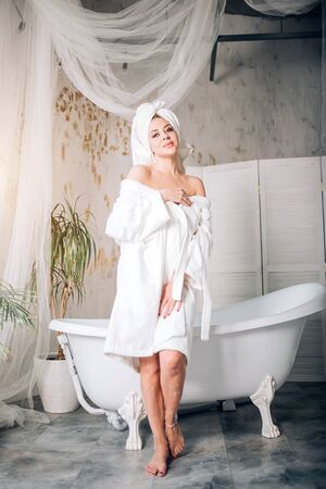Pleasant looking blonde lady smiling covering body with towel feeling happiness and pleasure after beauty treatments, getting spa, having aroma bath in modern comfortable bathroom.