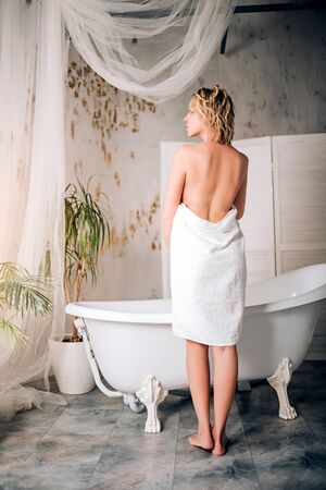 Purity, wellness and skin care. Backside portrait of slim woman with short blonde wet hair covering her body with white towel standing in front of the bath looking away in modern bathroom. Stock Photo