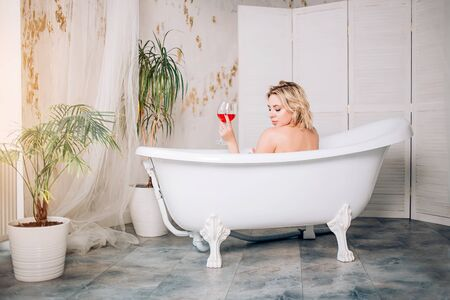 Backside portrait of naked female model sitting in warm bath with glasses of red wine enjoying spa procedure in sunny day, relaxing in modern luxury bathroom with green plants in hotel or at home.