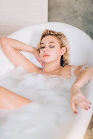 Attractive young caucasian naked woman with healthy white skin, short blonde hair, with closed eyes chilling in spa salon, taking foam bath with pleasure expression after working day.