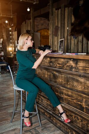 Full length portrait of blonde receptionist wearing elegant emerald color clothing, glasses, high heeled shoes sitting at reception desk using laptop in beauty salon with loft interior. Side view.