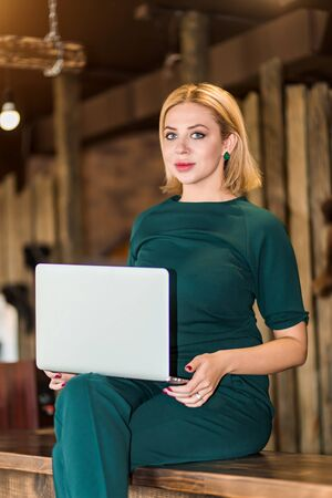 Cheerful elegant blonde business woman, administrator wearing emerald color suit sitting on wooden reception desk holding laptop, having fun in workplace in beauty salon with modern loft interior.
