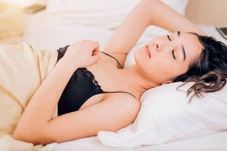 Attractive nice girl with fresh clean skin having rest under cream color blanket in comfortable bed in the morning, close up side view photo. Healthy sleep, free time, leisure and relaxation concept.