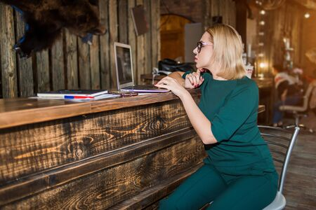 Side view of attractive blonde business woman, administrator with red manicure looking at screen of laptop with concentrated expression sitting at high reception desk against beauty salon background.
