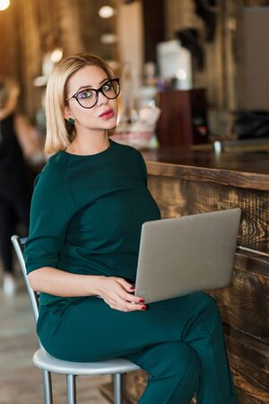 Serious tired elegant woman with short blonde hair, green earrings, wearing emerald color suit and glasses sitting with laptop near reception desk in beauty salon.