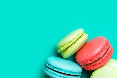 Close up of delicious fresh macaroon on turquoise background with copy space for confectioner, cafe, bakery 写真素材
