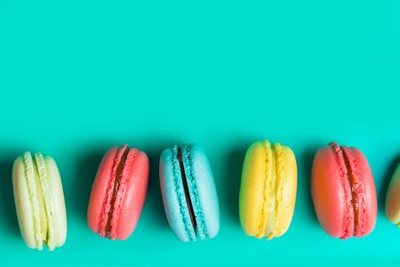 Cake a lot of colorful french cookies macarons on turquoise background with copy space