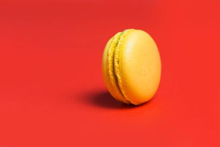 Closeup of one yellow sweet macaroon on red background. Sweet French pastries for tea. Copy space