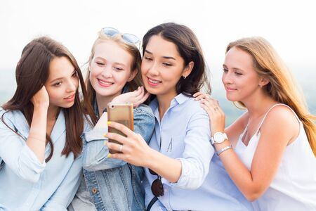 Close-up of four beautiful young female students doing selfies and smiling