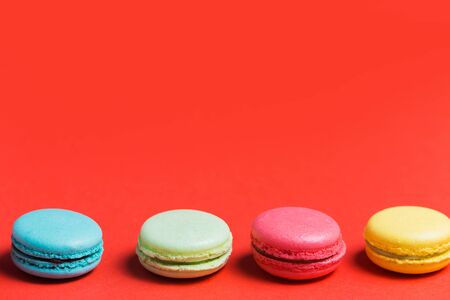 Sweet and colourful french macaroons or macaron on red background with copy space. Dessert, homemade cake