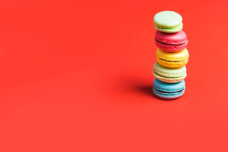 Minimalism. Bright red background for text with colorful macaroons on the edge of the photo, copy space