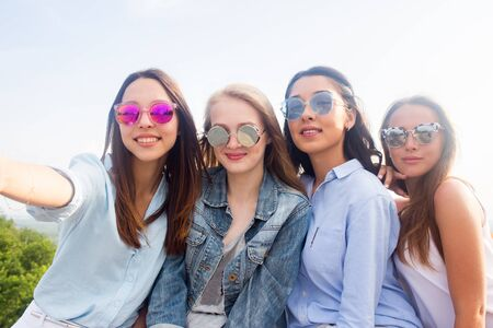 four beautiful young student girl in colorful sunglasses smiling and taking selfies outdoor, on the background of nature.