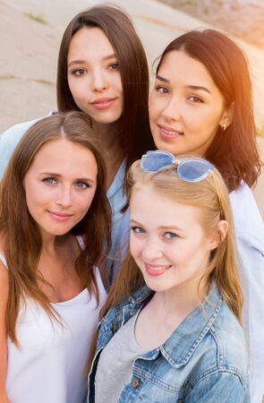 portrait of four femle friends looking friendly at camera, smile, happy. people, lifestyle, friendship concept Stock Photo